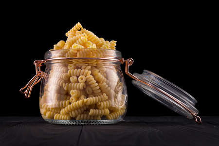 Jar of fusilli pasta on wooden table isolated on black background