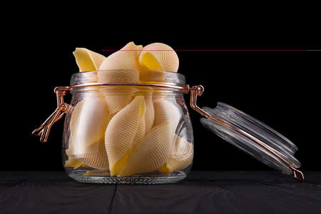 Jar of conchiglie pasta shell on wooden table isolated on black