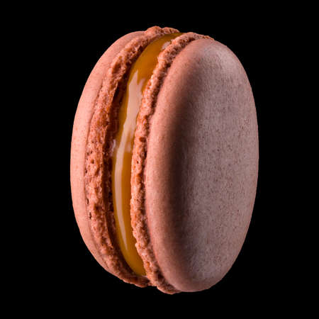French caramel macaroon or macaron isolated on black