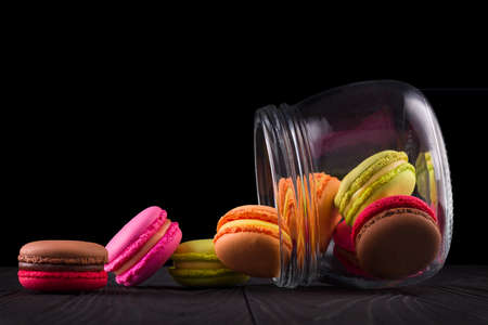 Jar of french colorful macaroon or macaron on wooden table isolated on black background with clipping path