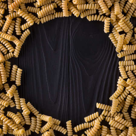 Top view of fusilli pasta on black wooden table with space for your text. Stock fotó