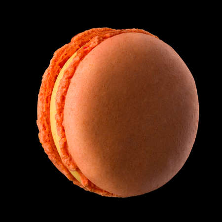Macro photo of french orange rose macaroon isolated on black with clipping path