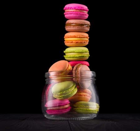 Jar of french macaroons and heap of them on black wooden table