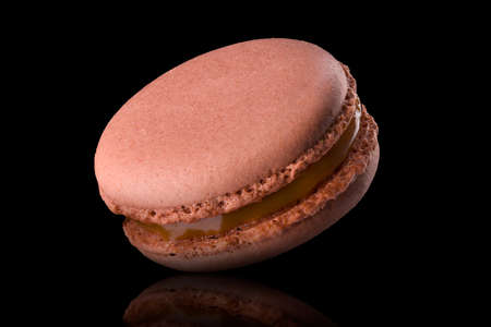Macro photo of french caramel macaroon with reflection isolated on black