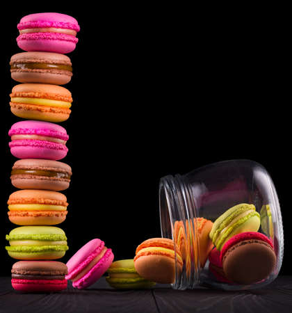 Jar of french colorful macaroons and heap on wooden table isolated on black