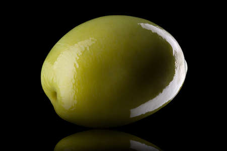 Macro photo of green olive with reflection of light isolated on a black