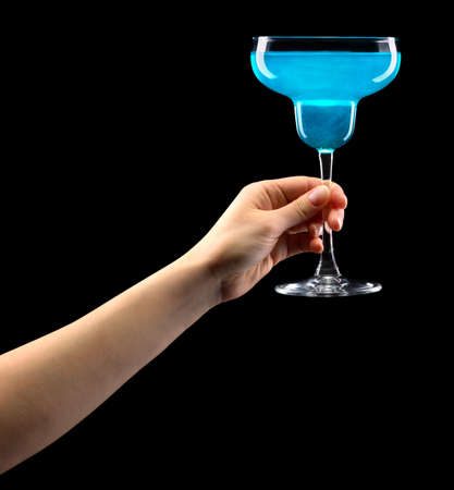 Woman hand holding margarita glass isolated on black. Banque d'images