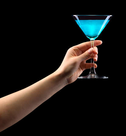 Woman hand holding blue martini glass isolated on black.