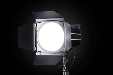 Photography studio flash isolated on black background with lamp. Proffetional equipment like monobloc or monolight