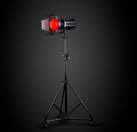 Photography studio flash on a lighting stand isolated on black background with lamp. Proffetional equipment like monobloc or monolight