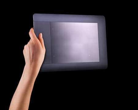 Hand holding graphic tablet for illustrators, designers and photographers isolated on black background with clipping path