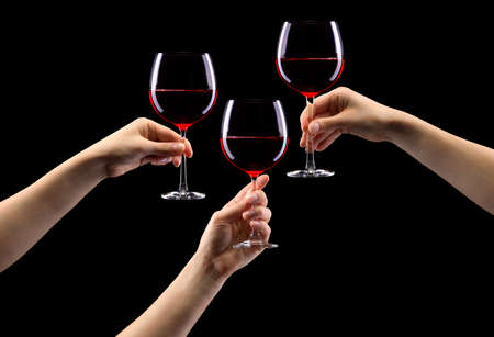 Set of hands holding red wine glass isolated on black.