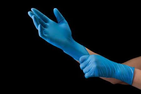 Doctor wearing a medical glove on hands isolated on black