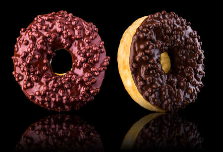 Set of glazed donuts with sprinkles on a black background