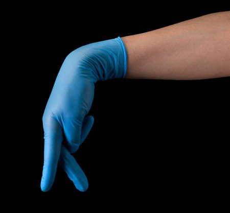 Doctors hand in sterile medical gloves show walking finger isolated on black