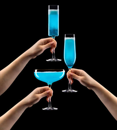 Set of hands olding glass of blue sparkling champagne isolated on black background.