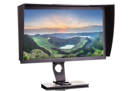 Professional photographer monitor with shading hood isolated on white background with wallpaper on a screen.