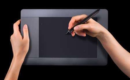 Hand holding digital graphic pen and drawing graphic tablet for illustrators, designers and photographers isolated on black background