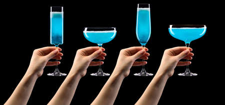 Set of hands holding glass of blue sparkling champagne isolated on black. Stock Photo