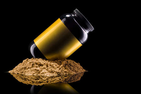 Plastic jar of sport nutrition like whey protein casein, bcaa, creatine on heap of powder isolated on black background . Concept of fitness supplement Stock Photo