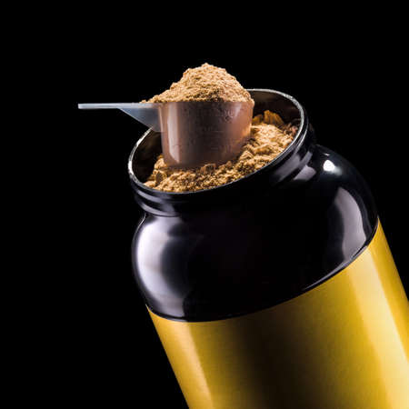 A scoop of chocolate protein powder drink in black plastic container isolated