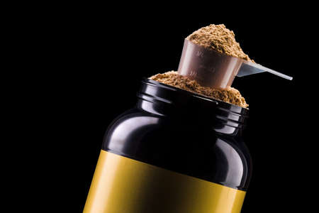 A scoop of chocolate protein powder drink in black plastic container isolated Stock fotó