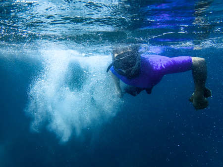 An image of a man diving in the sea underwater with lots of air bubbles