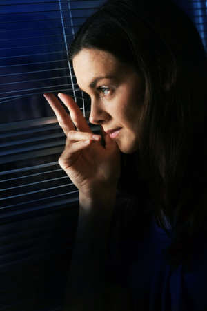 Woman is looking though window.