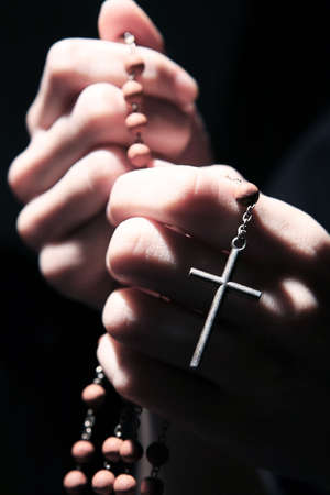 devout: Praying in the dark with a rosary.