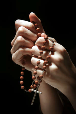 Praying in the dark with a rosary.