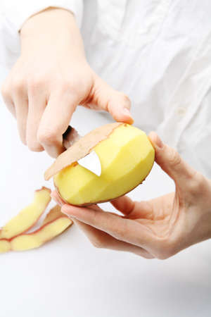 paring: Woman dressed in white peels a potato.