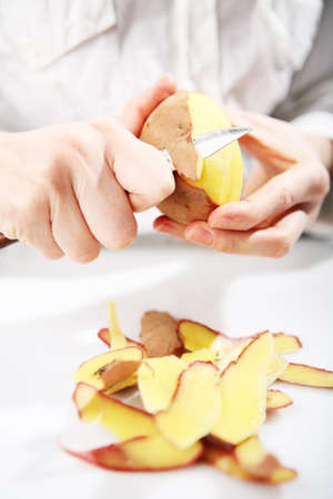 paring knife: Woman dressed in white peels a potato.