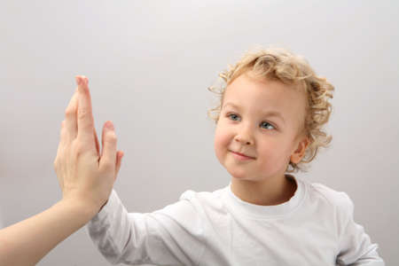 Child and adult clap hands.