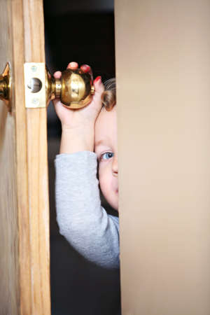 supervise: Kid open door. Stock Photo