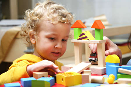Boy playing with colorful wooden blocks.
