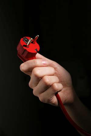 Hand holding power plug isolated on black background photo