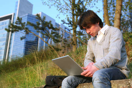 Young man working on a laptop outside. photo