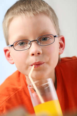 slurp: Child sipping orange juice through straw Stock Photo