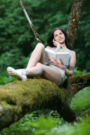 Woman sitting in the park and reading.  photo
