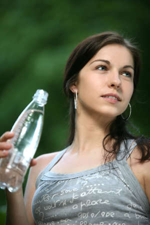 botle: Beautiful young woman in the park. Drinks water. Stock Photo