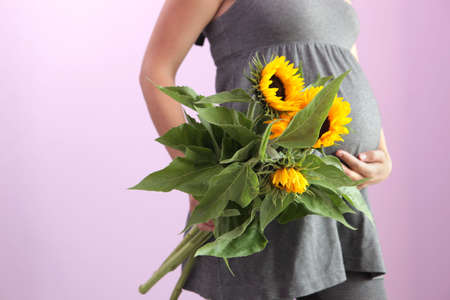 Pregnant woman holding yellow flowers. photo