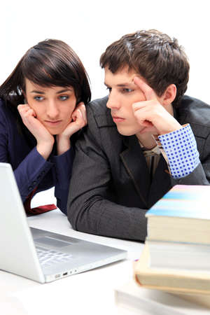 joyless: Unhappy young couple looking at laptop