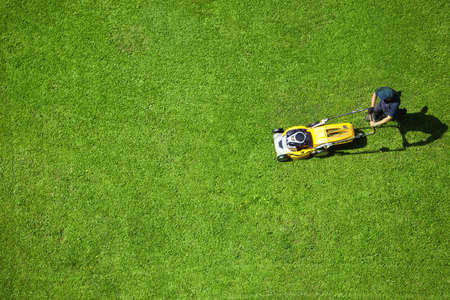 mower: A man mowing the lawn Stock Photo