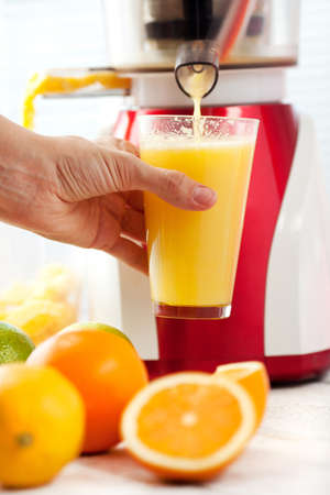 Slow juicer and orange juice  Stock Photo