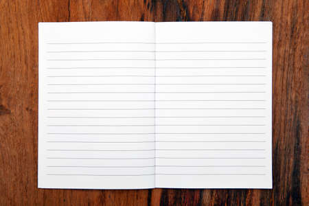 open diary: Open notebook on wooden table. Lined paper background.