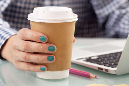 take a break: Young woman drinking coffee from disposable cup