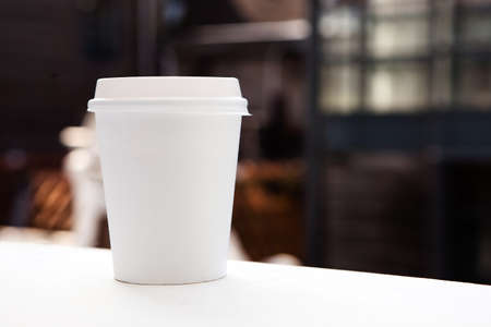 coffee mugs: Disposable coffee cup on windowsill with city in background. Stock Photo