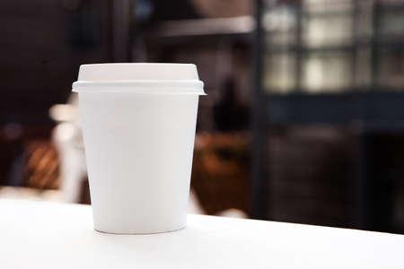 filiżanka kawy: Jednorazowy kubek kawy na parapecie z miastem w tle. Zdjęcie Seryjne