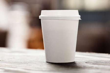 take a break: Disposable coffee cup on windowsill with city in background. Stock Photo
