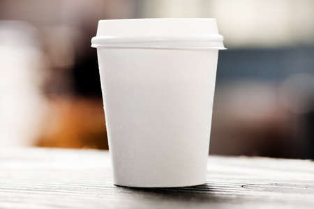 Disposable coffee cup on windowsill with city in background. Stock Photo